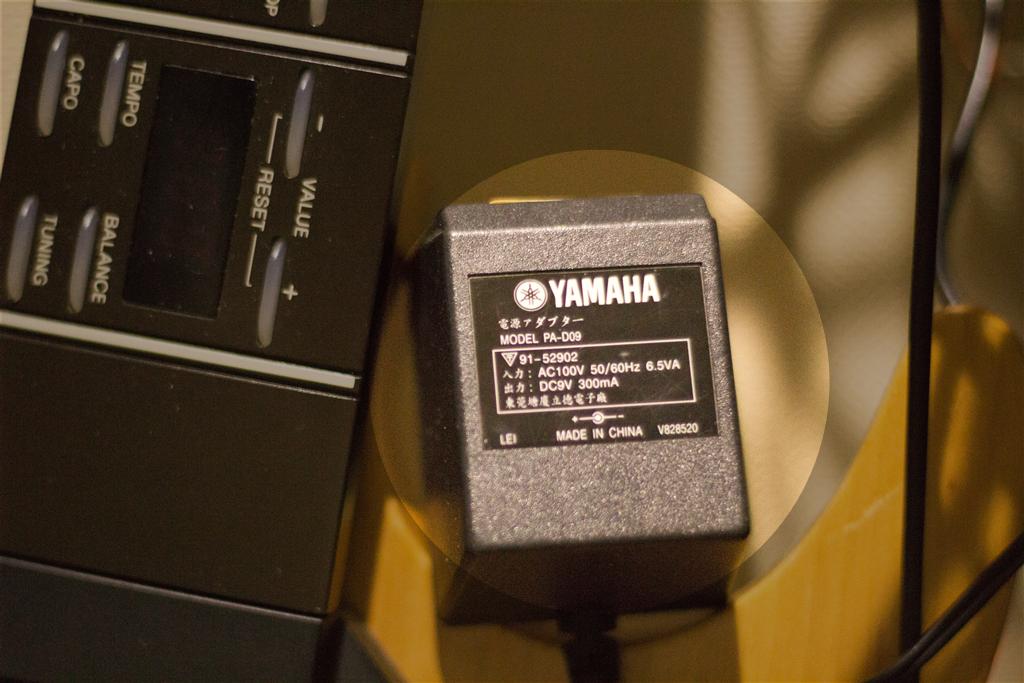 YAMAHA EZ-EG 付属の9V・ACアダプター。コンパクトエフェクター用の9V と異なってプラグの外側がマイナスなので要注意です。